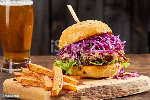 istock Sandwith with pulled pork and french fries on wooden background 679661300