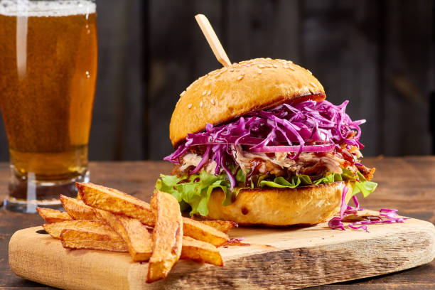 Sandwith with pulled pork and french fries on wooden background stock photo
