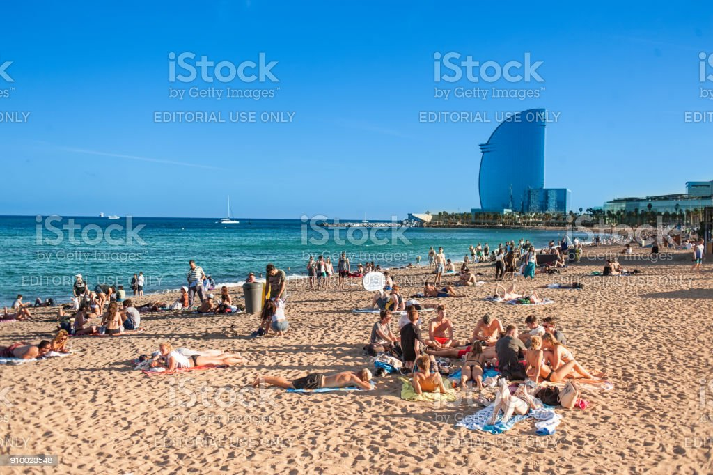 Sandy Barceloneta beach in Barcelona with W hotel on a background and people enjoying a sunny day stock photo