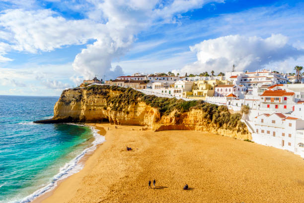 sandy beach between cliffs and white architecture in carvoeiro, algarve, portugal - portugal stock photos and pictures