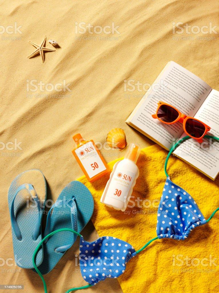 Sandy Beach with a Bikini, Book and Sun Cream royalty-free stock photo