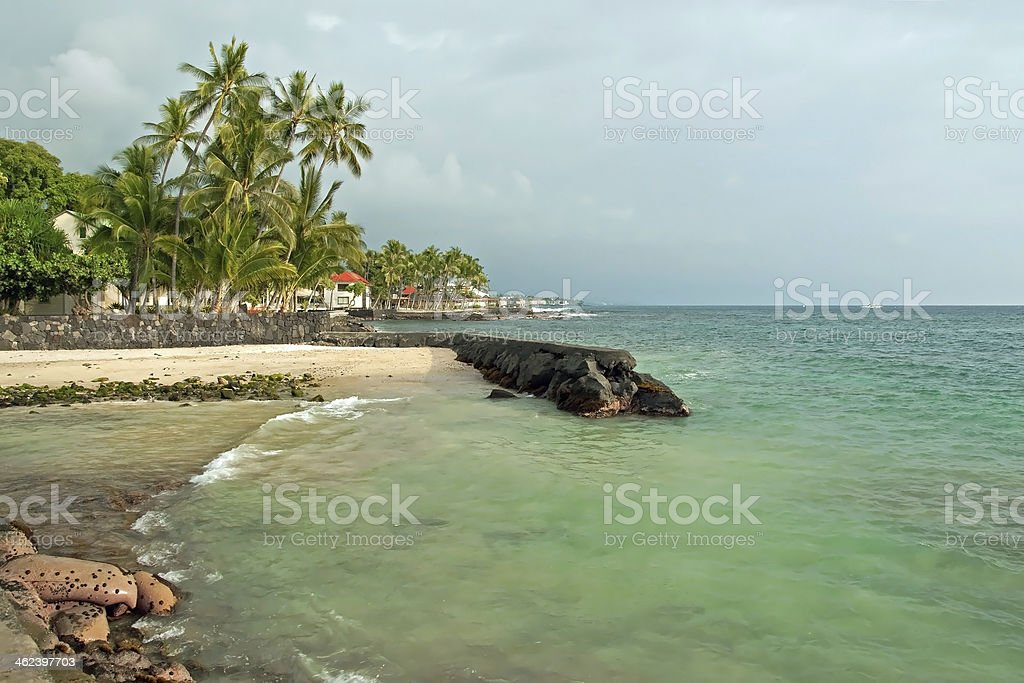 Sandy beach with azure ocean and palm trees during storm royalty-free stock photo