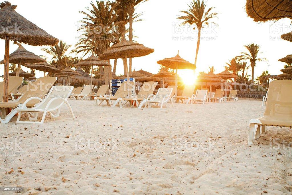 Sandy beach with deckchairs stock photo
