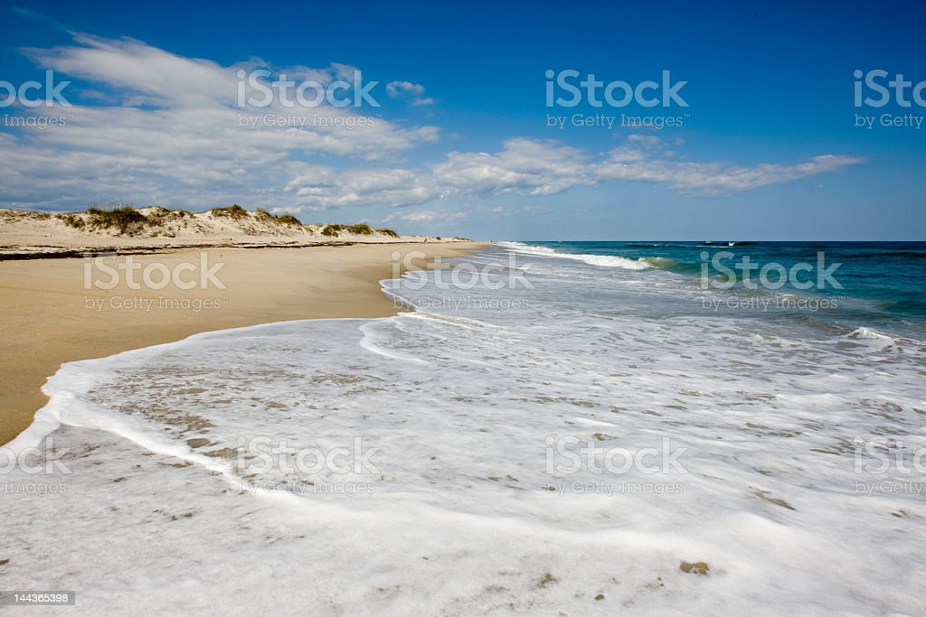 Sandy beach with foamy ocean waves stock photo