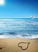 Sandy beach with heart shape and sailing boat on the horizon over clear sky in Antalya, Turkey
