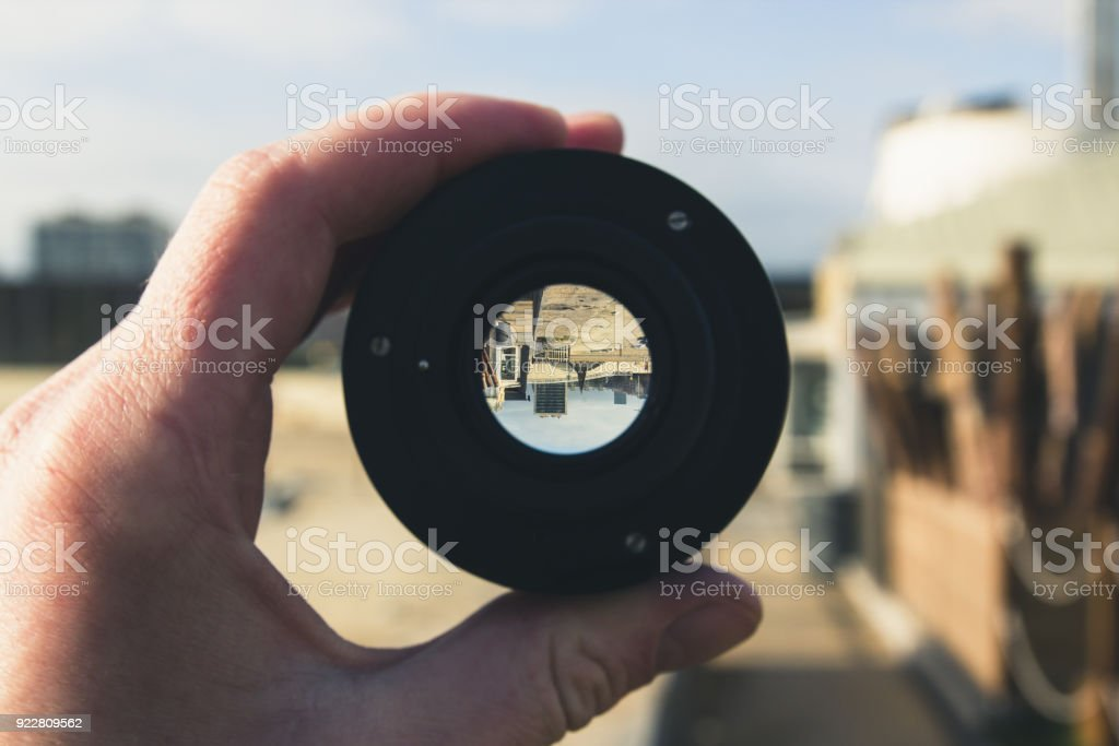 Sandy beach with Playground and houses in the background, view through the lens, image inside is inverted stock photo