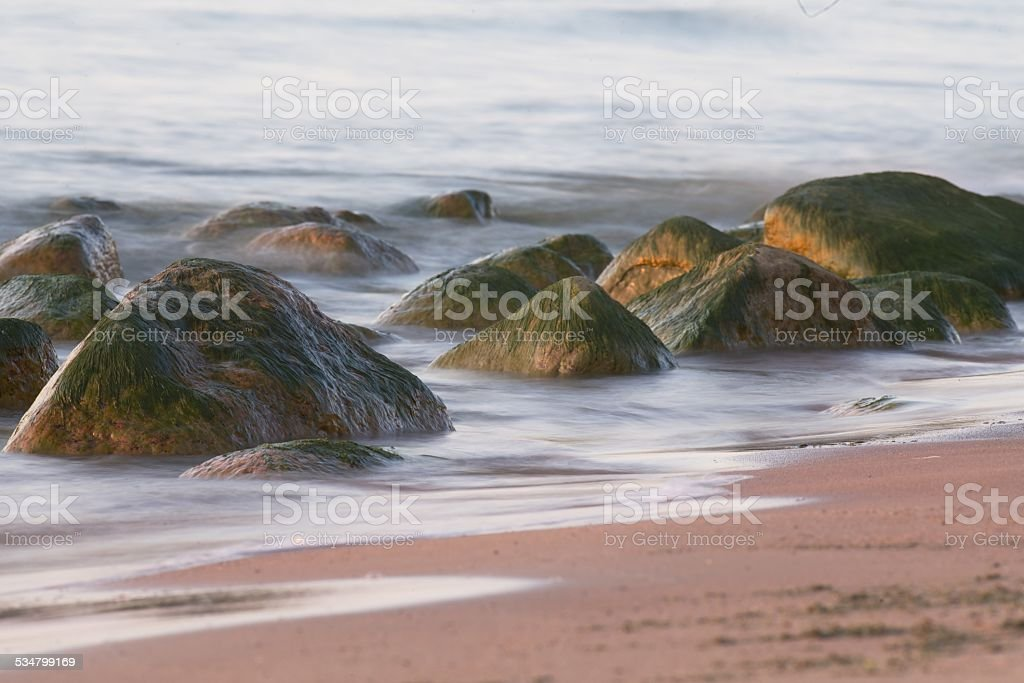 Sandy beach with stones stock photo