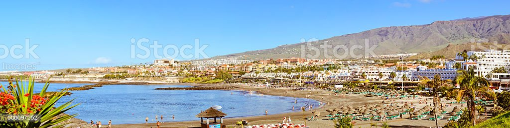 Sandy beach with thatched parasols and sunbeds, Costa Adeje stock photo