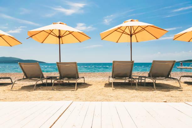 Sandy beach with umbrellas and sunbeds on Adriatic sea. stock photo