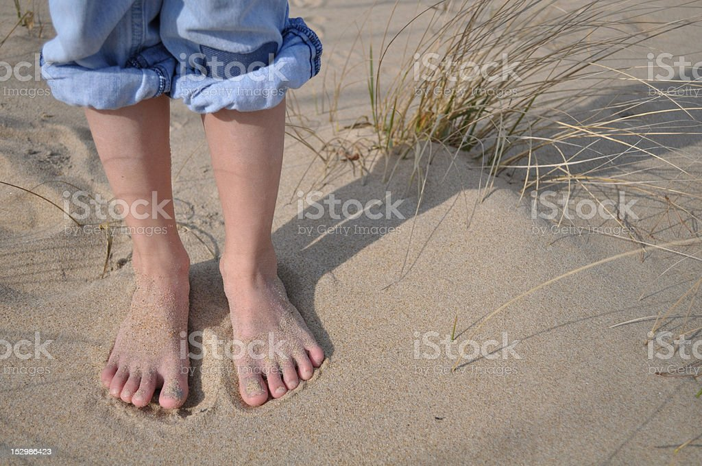 Sandy child's feet at the beach royalty-free stock photo