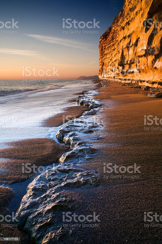 Sandy Cliffs Along Beach at Sunset royalty-free stock photo