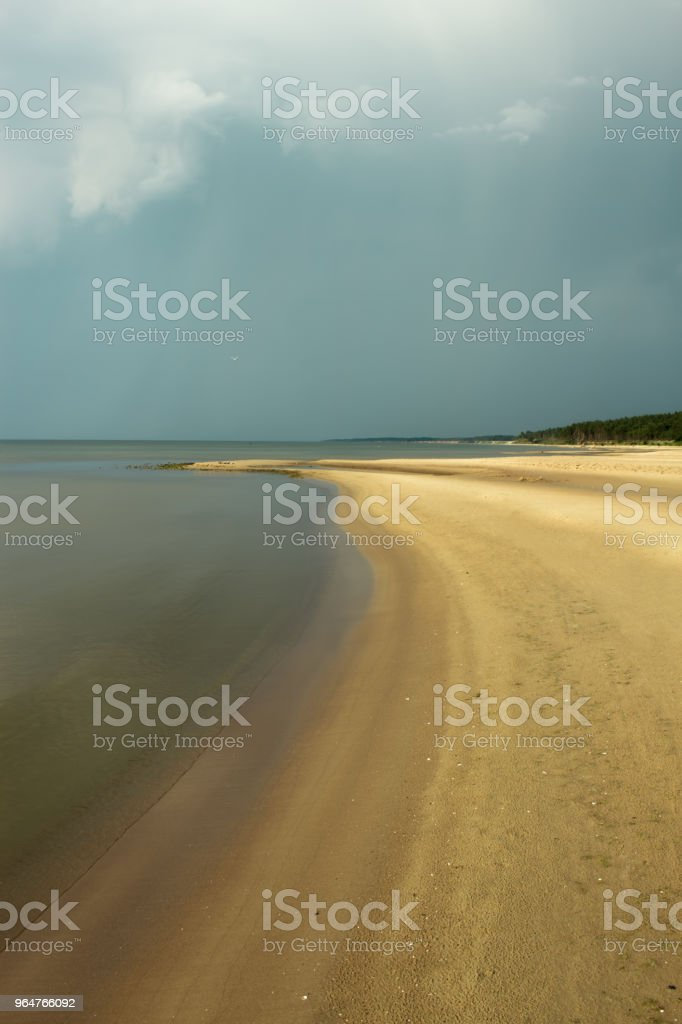 Sandy coast of the Baltic Sea, a breeze, white clouds on a dark sky on the horizon after a summer rain in Latvia, Pavilosta. royalty-free stock photo