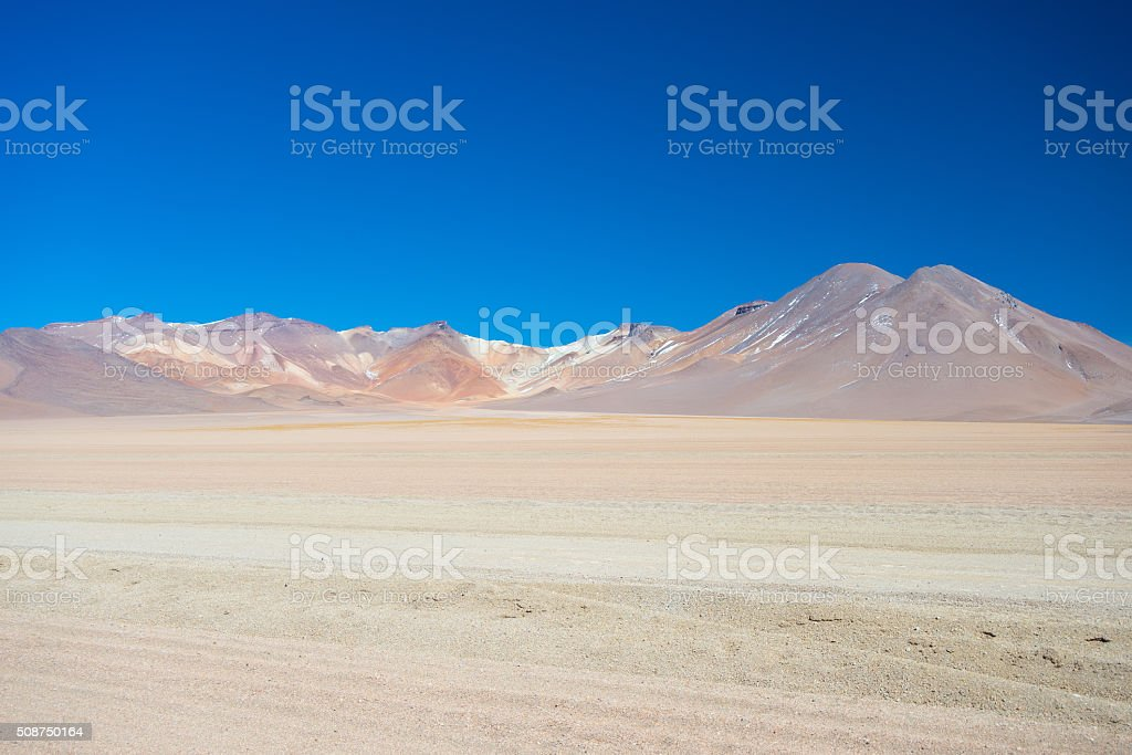 Sandy desert stretch and volcano on the Bolivian Andes stock photo