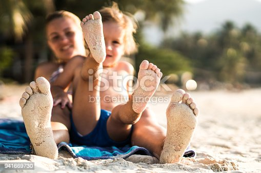 istock Sandy feet of a mother and son on the beach. 941669730