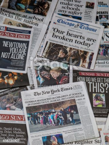 Carol Stream, IL, USA, December 22, 2012: Sandy Hook school shooting collage. A pile of local and national newspapers, many of them with headlines on the front pages reporting stories in the days immediately following the school shooting at sandy hook, Newtown CN.
