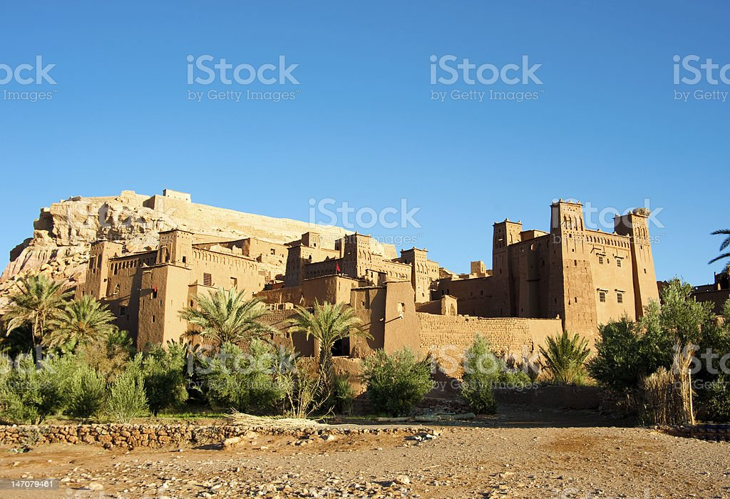 Sandy Kasbah surrounded with green plants in Morocco royalty-free stock photo