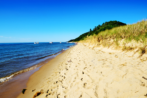 Sandy shore of Lake Michigan at Saugatuck Dunes State Park in Allegan County, Michigan. Distant people and moored boats.