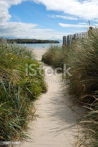 A Sandy pathway with grass reeds on each side and a wooden fence on the right leading to a beautiful bay with calm blue sea and an island in the middle of the bay the sky is blue with white fluffy clouds the figures of three people and a boat are in the distance. Rhoscolyn, Anglesey, North Wales, United Kindom, UK,