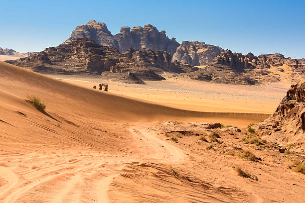Sandy Road in the Wadi Rum Desert Jordan Stock photo of a desert road leading through the  Wadi Rum Desert also known as the Valley of the Moon, a UNESCO World Heritage Site in Jordan. riverbed stock pictures, royalty-free photos & images