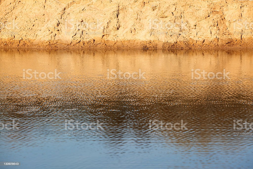 sandy shore reflected in the water royalty-free stock photo