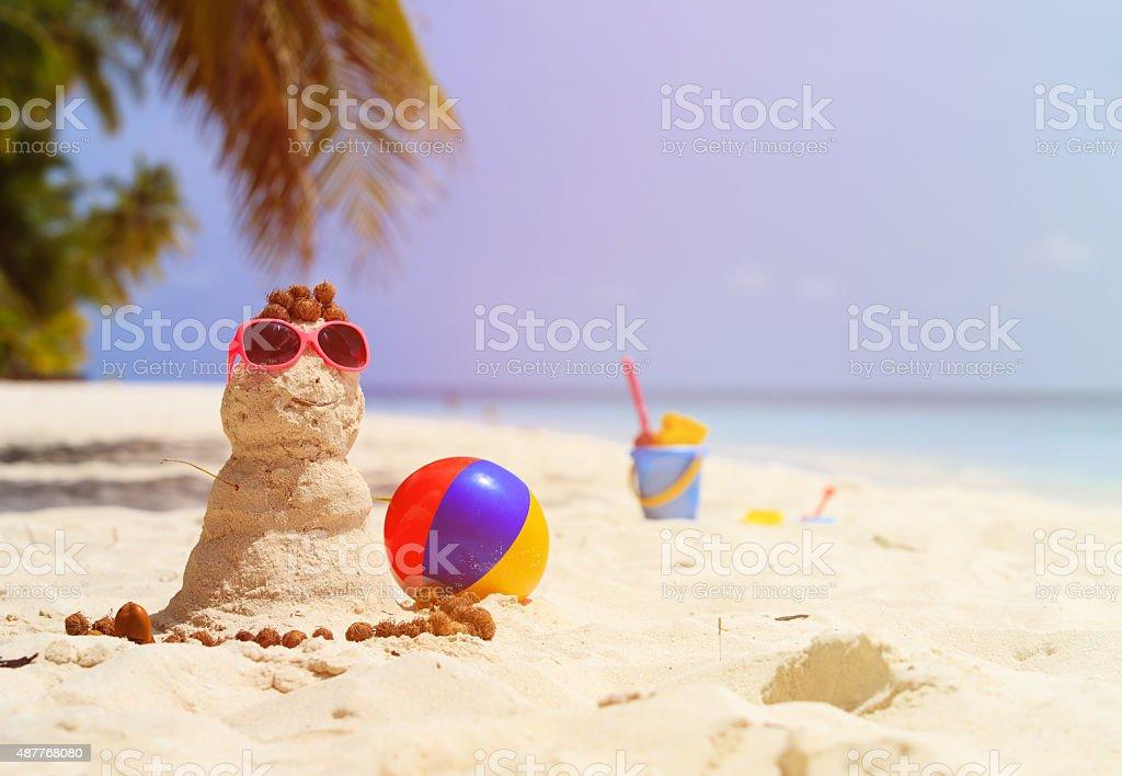Sandy snowman and toys at sand beach stock photo