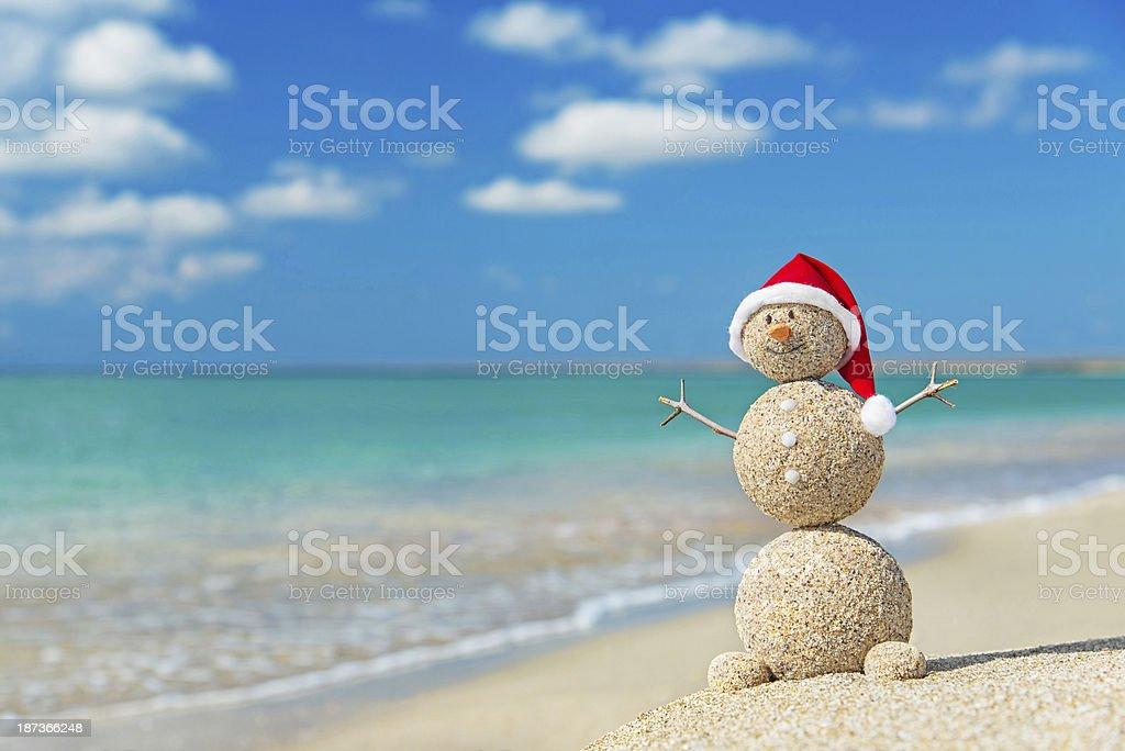 Sandy snowman in Christmas santa hat stock photo