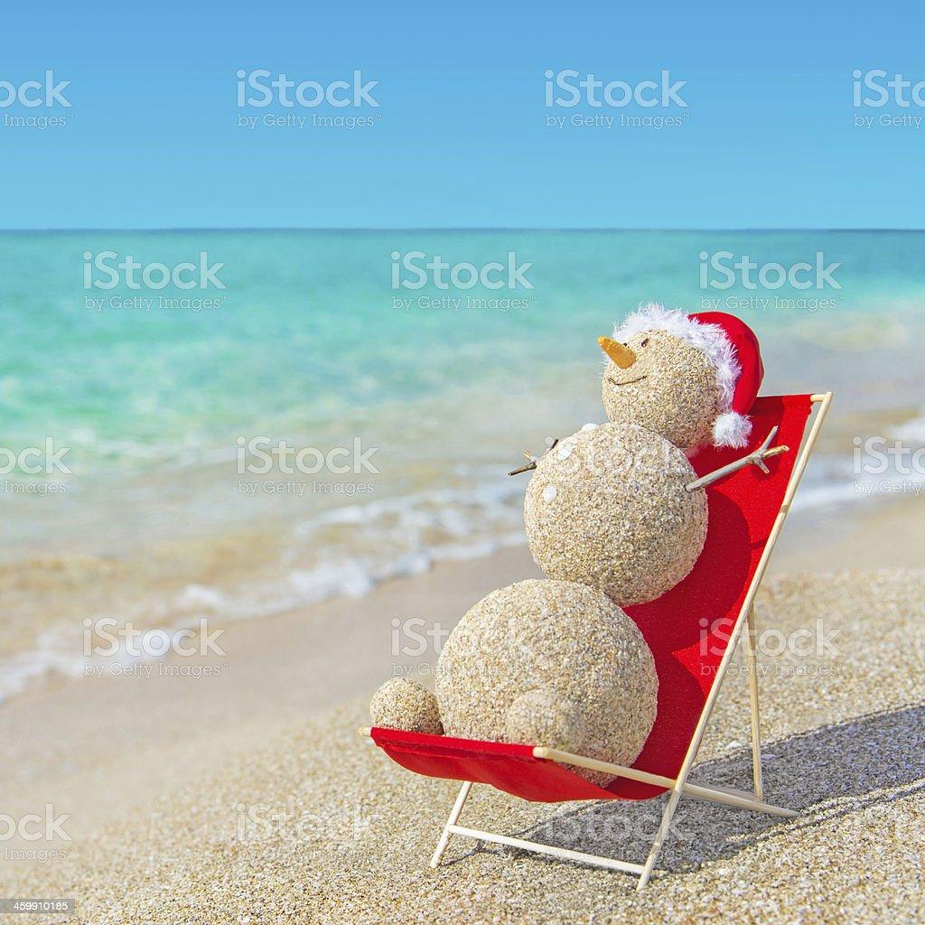 Sandy snowman in Christmas santa hat sunbathing at beach lounge. stock photo