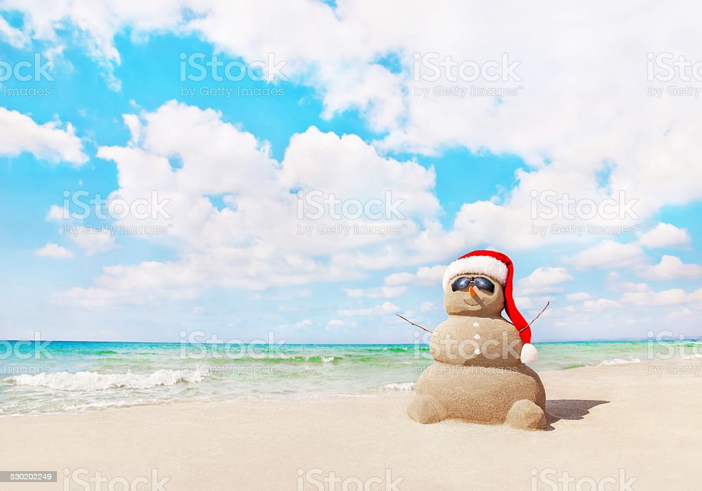 Sandy snowman in santa hat at beach. Christmas concept stock photo