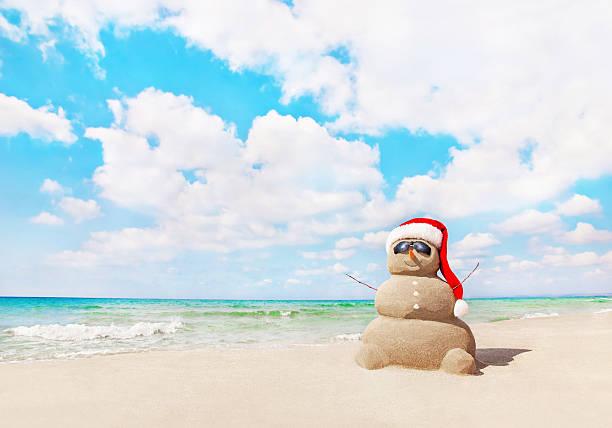 sandy bałwan śniegowy w santa hat na plaży. boże narodzenie koncepcja - new year zdjęcia i obrazy z banku zdjęć