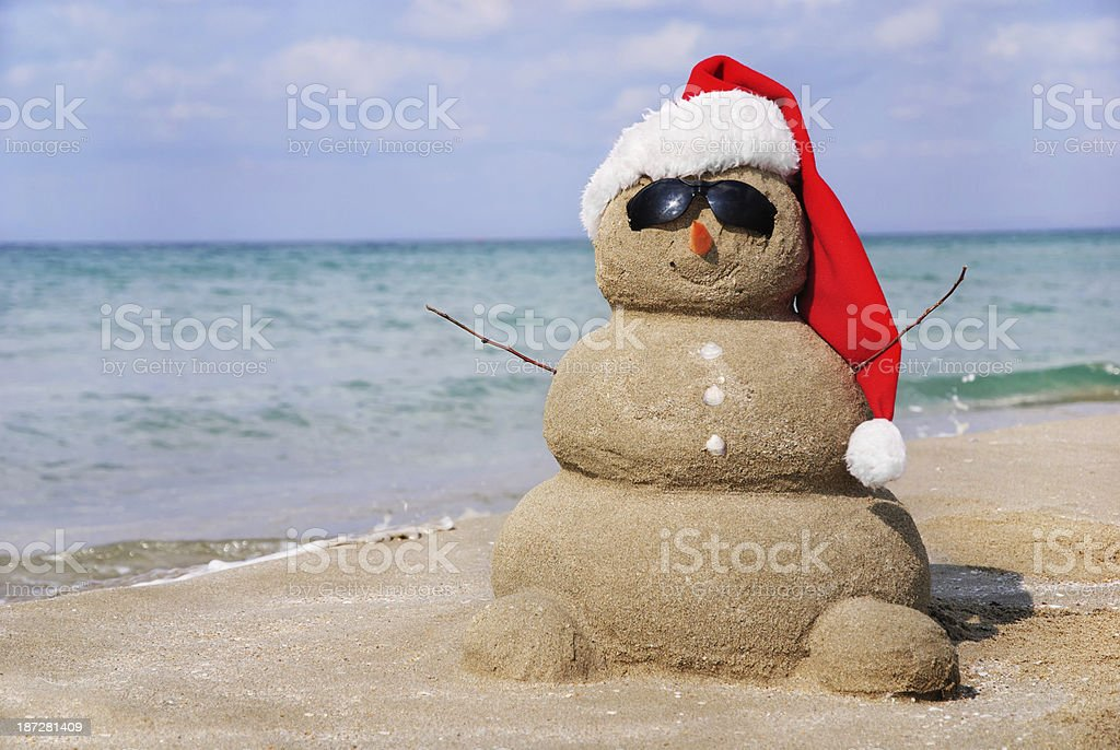 Sandy snowman in santa hat. Christmas holiday concept stock photo