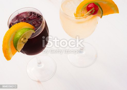 Photograph of a glass of sangria and a glass of chilled, iced wine.