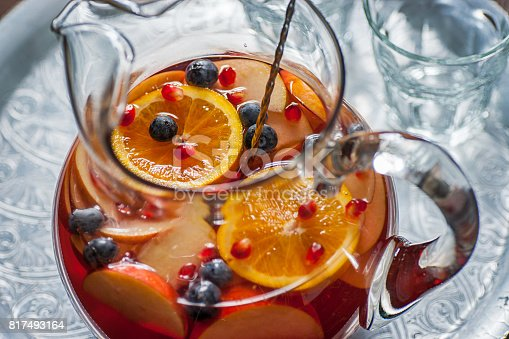 High resolution digital capture of a glass pitcher filled with sangria. This sangria combines rose wine, red wine, and sparkling wine with various fresh fruits and berries, including blueberry, orange, apple, and pomegranate. Pitcher sits on a metal tray next to a pair of glasses, and there is a mixing spoon inside the pitcher. Somewhat shallow depth of field, with sharp focus on the surface of the sangria, highlighting the fresh fruits.