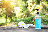 istock Sanitary mask and alcohol gel for hand washing and cleaning on a wooden table. 1217354589