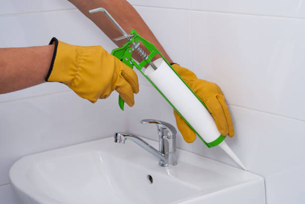 sanitary silicone sealant plumber fills the seam between the sink and the tile with a silicone sealant silicon stock pictures, royalty-free photos & images