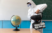 istock Sanitising the world. Man in protective suit and mask sanitising and sterilises classroom and items inside to prepare for education 1271796130
