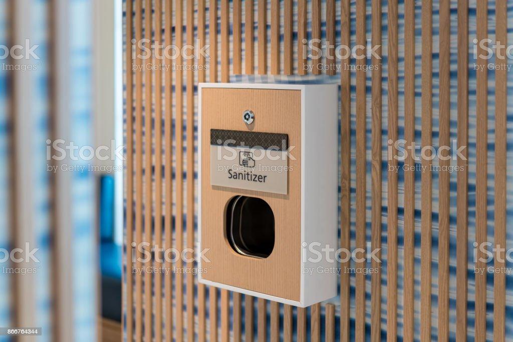 Sanitizer machine outside public bathroom stock photo