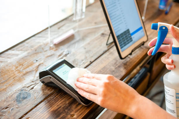 Sanitizing a contactless payment terminal for COVID safety Safety protocol for reopening during the COVID-19 pandemic. retail equipment stock pictures, royalty-free photos & images