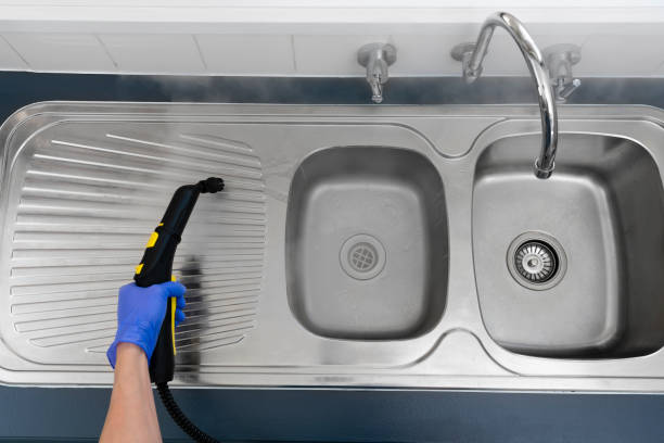 Sanitizing kitchen sink with steam cleaner stock photo