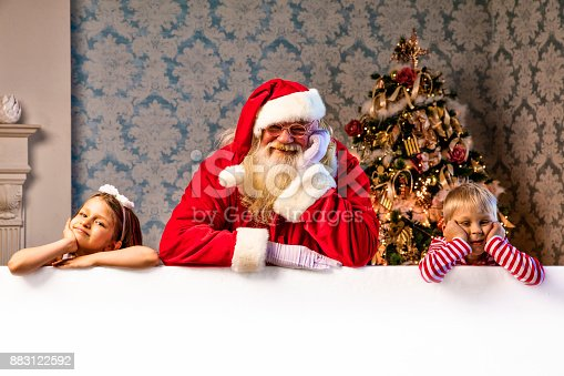 istock Santa and kids pointing on blank banner 883122592