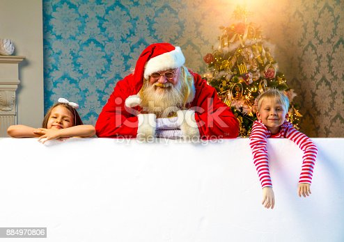istock Santa and kids pointing on blank banner 884970806