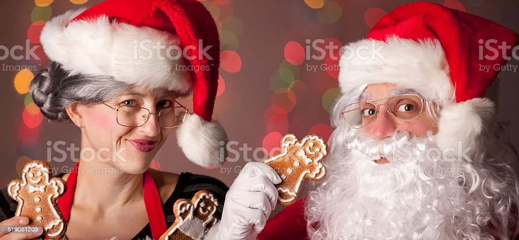 Santa and Mrs. Claus Holding Gingerbread Cookies stock photo