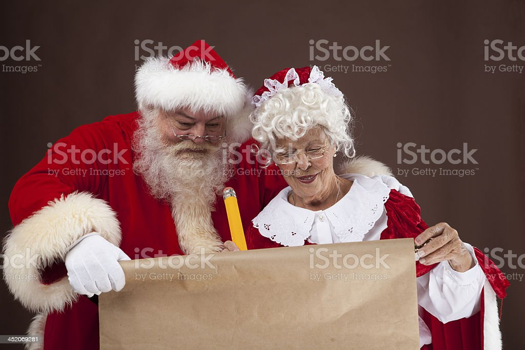 Santa and Mrs Claus writing on the naughty nice list stock photo