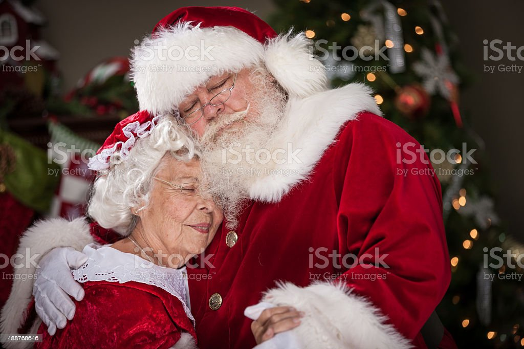 Ms. Claus and Santa have a real good time embracing affectionately...