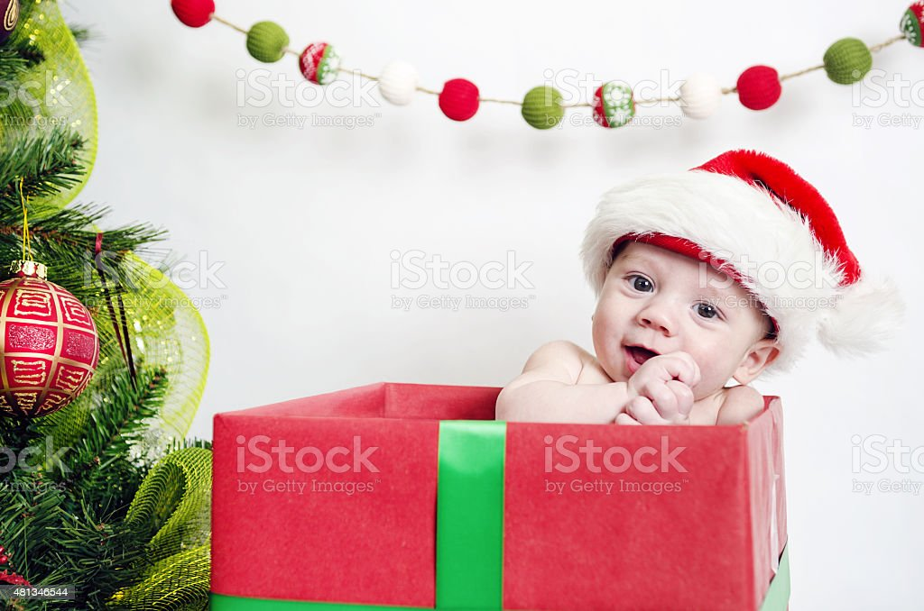 A young baby is ready for his 1st Christmas, wearing a festive...