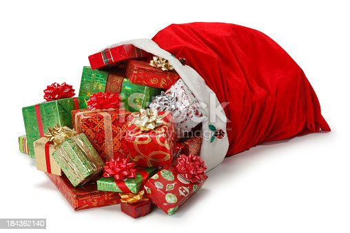 Christmas presents spilling out of Santa Claus' red bag as it lies on it's side.  Photographed on white background in a studio setting. A clipping path is included.