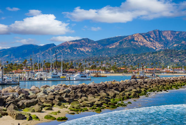 Santa Barbara Marina shoreline breakwater with recreational boats, CA moored recreational boats; California marina scene; safe harbor; Southern California recreation; Santa Barbara Harbor, mountain range, leisure boats, water reflections, clear sky, still water, breakwater santa barbara california stock pictures, royalty-free photos & images