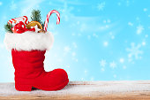 Santa boots with sweets and gifts on a blue background with falling snowflakes