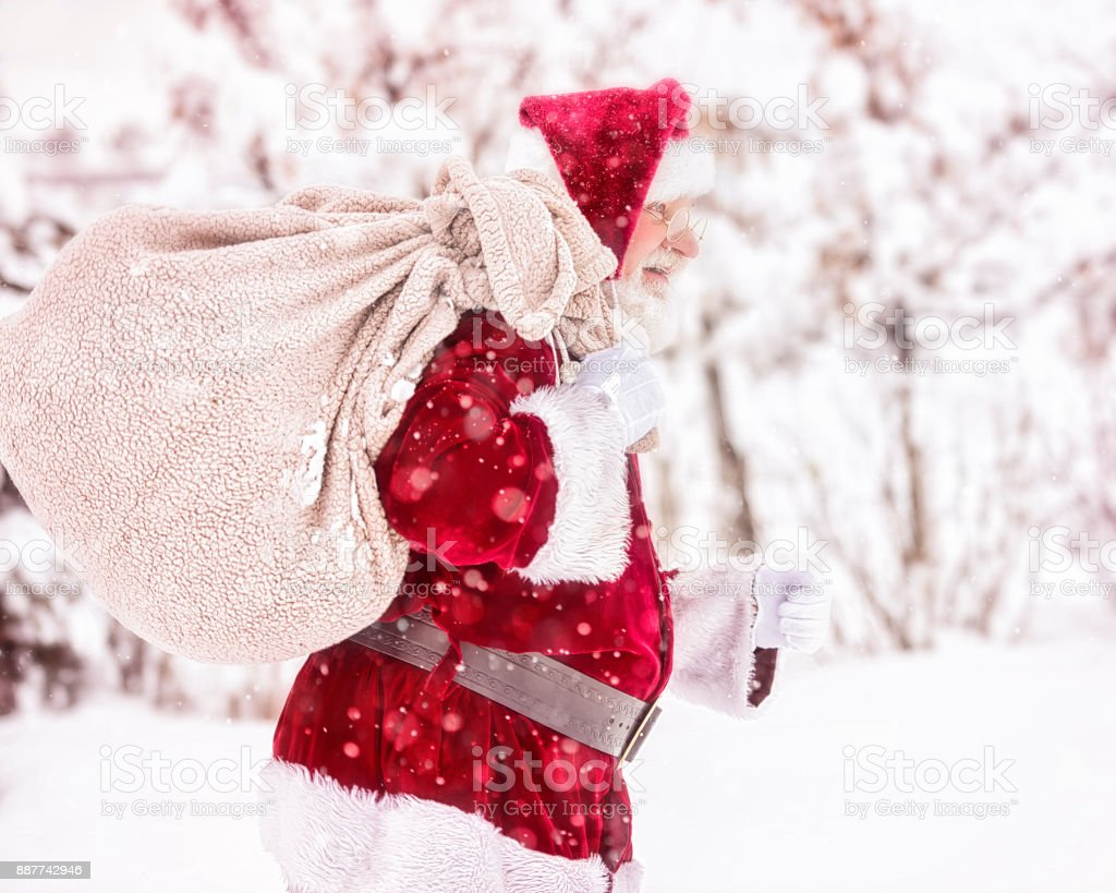 Santa Braving a Cold Winter Snow Storm To Carry Presents to Deserving Children stock photo