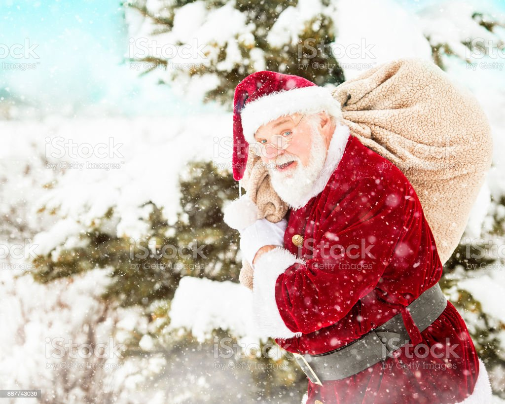 Santa Carrying His Pack Of Toys In A Winter Storm stock photo