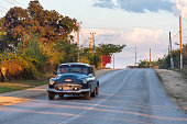 Santa Clara, Villa Clara, Cuba-March 27, 2019: Obsolete vintage car driving in a rural road during the sunset hours. Old American cars driving are a common scene in the island